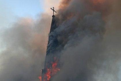 El humo envuelve una iglesia que fue incendiada durante una protesta contra el gobierno de Chile, en el primer aniversario de las protestas y disturbios que sacudieron la capital en 2019, en Santiago, Chile. REUTERS/Ivan Alvarado