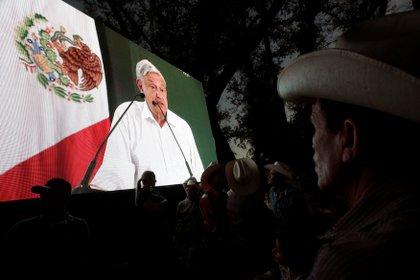 La gente mira al presidente de México, Andrés Manuel López Obrador, en una pantalla de video durante un evento en Badiraguato, en el estado mexicano de Sinaloa, México, 15 de febrero de 2019. REUTERS / Daniel Becerril