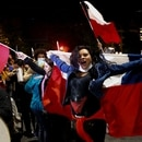 A woman holds a Chilean flag as she reacts to the referendum on a new Chilean constitution in Valparaiso, Chile, October 25, 2020. REUTERS/Rodrigo Garrido