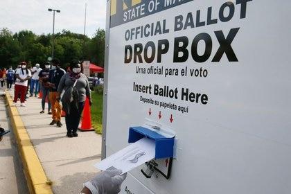Millones de estadounidenses ya están votando en forma anticipada en diferentes estados. Un votante coloca su boleta en una urna electoral, mientras otros votantes esperan en una larga fila para emitir sus votos en College Park, Maryland. REUTERS/Jim Bourg