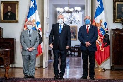 El presidente chileno, Sebastián Piñera (al centro), el nuevo ministro de Salud, Óscar Enrique Paris (a la izquierda), y el exministro de Salud Jaime Mañalich asisten a un cambio de gabinete en el Palacio de Gobierno, en medio de la pandemia de COVID-19, la enfermedad causada por el coronavirus.