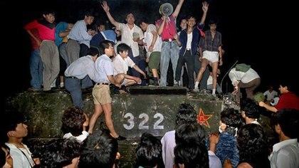 Un grupo de jóvenes sobre un tanque cerca de la Plaza Tiananmén