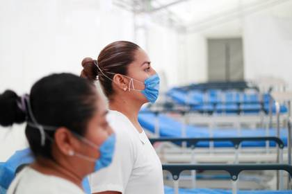 Two nurses wearing protective masks pose inside the new immediate response mobile hospital with 50 intensive care beds against the outbreak of coronavirus disease (COVID-19) in Pachuca, Hidalgo, Mexico, March 19, 2020. Picture taken March 18, 2020. REUTERS/Henry Romero