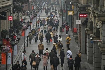 Personas caminan en una calle peatonal de Wuhan. (Hector RETAMAL / AFP)