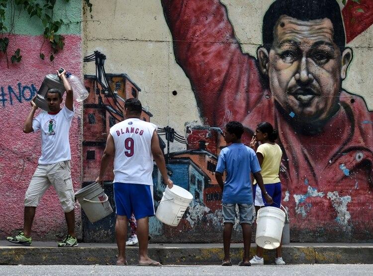 Personas buscan agua en Caracas tras el masivo apagón que afectó Venezuela en marzo (JUAN BARRETO / AFP)