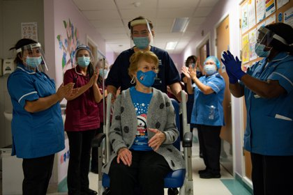 Margaret Keenan, de 90 años es aplaudida por el personal del Hospital Universitario de Coventry, en el Reino Unido. La mujer se convirtió en la primera británica en recibir la dosis de Pfizer contra el coronavirus (Reuters)