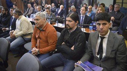 """Lázaro Báez (buzo naranja) con su hijo Martín Báez a la derecha, en una de las audiencias por la """"ruta del dinero K"""""""