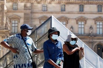 Personas con máscaras protectoras caminan cerca del Museo del Louvre
