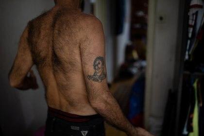 Abdou Batrouni, que tiene un tatuaje de Jesucristo en el brazo, se encuentra en una habitación de su casa que resultó dañada por una explosión en el puerto de Beirut, en el barrio de Karantina, Beirut, Líbano, el 13 de agosto de 2020.