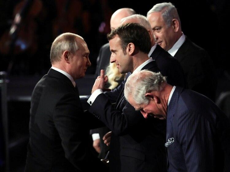 El presidente francés Emmanuel Macron conversa con su homólogo ruso, Vladimir Putin, durante la ceremonia. Foto: Abir Sultan/REUTERS