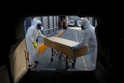 Foto de archivo. Trabajadores de una funeraria transportan el cuerpo de una persona que murió por la enfermedad del coronavirus (COVID-19) dentro de un ataúd de cartón, después de recogerlo de un hospital en la Ciudad de México, 5 de junio de 2020.. REUTERS/Carlos Jasso
