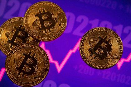 Una representación de la moneda virtual Bitcoin se ve delante de un gráfico bursátil en esta ilustración publicada el 15 de marzo de 2021. REUTERS/Dado Ruvic