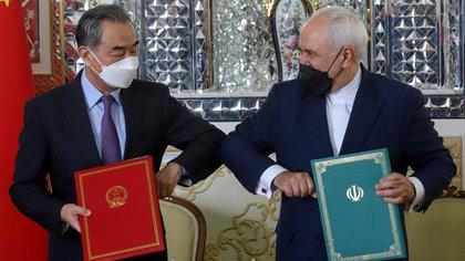 El diplomático y ministro de Relaciones Exteriores de la República Popular China, Wang Yi, y su par iraní, Mohammad Javad Zarif, chocan sus codos durante una reunión en Teherán (REUTERS)