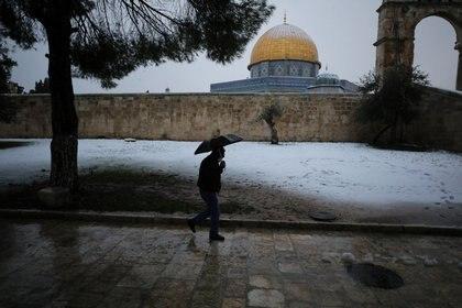 Un hombre camina junto a la Cúpula de la Roca durante una mañana nevada en la Ciudad Vieja de Jerusalén, el 18 de febrero de 2021. REUTERS / Ammar Awad