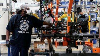 Los técnicos de ensamblaje de Dana Inc. utilizan máscaras para ensamblar ejes para fabricantes de automóviles en la planta de Dana en Toledo, Ohio (Reuters)