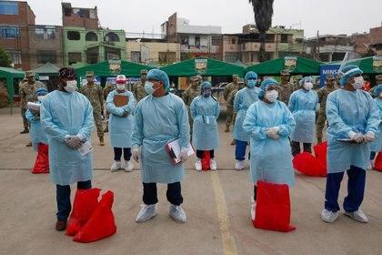 Trabajadores de la salud y soldados se ven antes de la realización de pruebas masivas por COVID-19, en Lima, Perú
