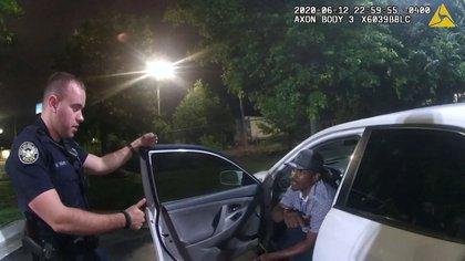 Capturas de pantalla del video de la Policía que muestra al agente Garrett Rolfe y al afroamericano Rayshard Brooks conversando antes de que el joven intentara huir