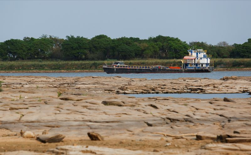 Un barco viaja en el río Paraguay, que fluye hacia el río Paraná, mientras la falta de lluvias en Brasil, donde el río se origina, ha hecho caer los niveles de agua, obligando a las embarcaciones de carga a reducir la cantidad de granos que transportan para su exportación (Reuters)