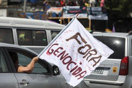 Grupos de personas en sus coches participan una caravana en apoyo a la petición de realizar un juicio político al presidente de Brasil, Jair Bolsonaro, por su cuestionada gestión frente a la pandemia del coronavirus hoy, en el centro de Río de Janeiro (Brasil). EFE/ Fabio Motta