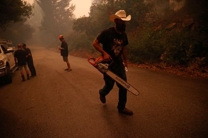"""Isaiah Klinger, que se encuentra entre un grupo de amigos que se hacen llamar """"Rescue One"""", lleva una motosierra por una carretera durante el incendio del complejo relámpago CZU en las afueras de Santa Cruz, California (Reuters)"""