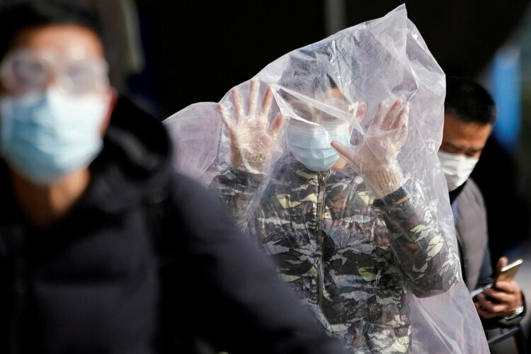 A passenger wearing a mask and covered with a plastic bag walks outside the Shanghai railway station in Shanghai, China, as the country is hit by an outbreak of a new coronavirus, February 9, 2020. REUTERS/Aly Song TPX IMAGES OF THE DAY