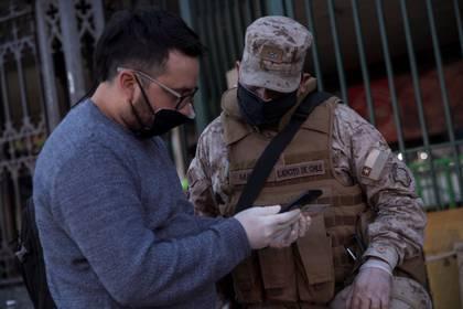 Militares con tapabocas hacen un control este jueves a los ciudadanos que entran a la Vega Central, principal mercado de abastos de Santiago (Chile). EFE/Alberto Valdés