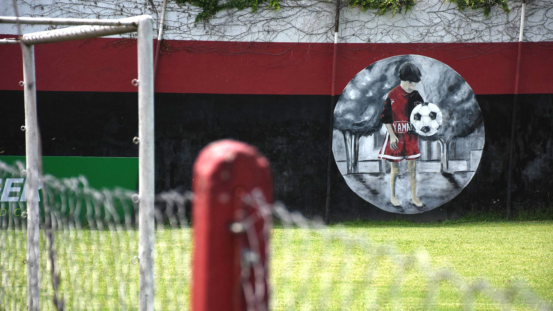 El mural con el Messi niño parece contemplar la canchita donde cientos de chicos pasan por allí soñando con ser Messi. (Leo Galletto)