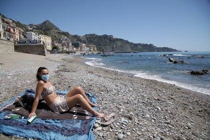 Una mujer con una máscara protectora se baña en la playa de Naxos, usualmente un punto turístico en Sicilia, mientras Italia comienza a aliviar algunas de las restricciones en Taormina, Italia, 12 de mayo de 2020 (REUTERS/Antonio Parrinello)