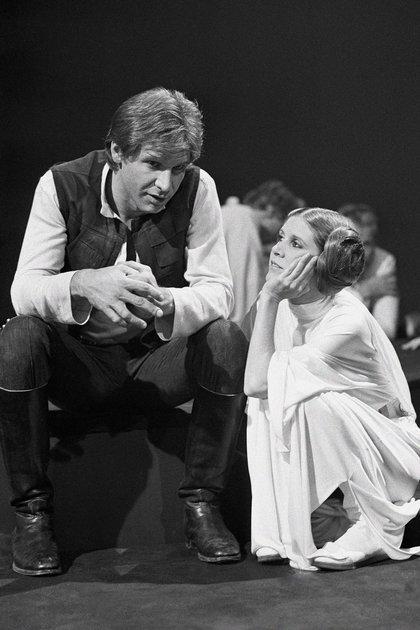 Harrison Ford habla conCarrie Fisher durante un descanso en la filmación de la película de Star Wars (AP Photo/George Brich, File)