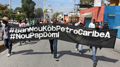 """Manifestantes sostienen una bandera con la leyenda """"¿Dónde está el dinero de Petrocaribe?"""" en Haití. (REUTERS/Andres Martinez Casares)"""