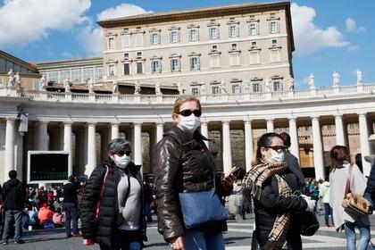 Turistas usan mascarillas frente a las ventanas cerradas del Palacio Apostólico del Vaticano que da a la Plaza de San Pedro y donde el Papa Francisco generalmente entrega su oración del Ángelus (Reuters)