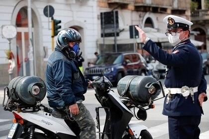 Un motociclista usa una máscara protectora junto a un oficial de policía, durante el brote de la enfermedad por coronavirus (COVID-19), en Bari, Italia (Reuters)