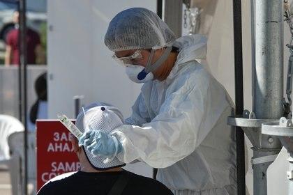 Un enfermero recoge un hisopo de un hombre con síntomas de COVID-19 (REUTERS/Mariya Gordeyeva)