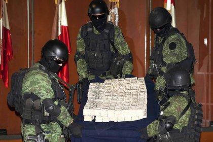 Soldados mexicanos muestran el secuestro de miles de dólares a capos narcos en una presentación ante los medios en la Ciudad de México (AP)
