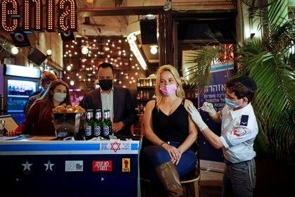 Una mujer recibe una vacuna contra el COVID-19 como parte de una iniciativa del municipio de Tel Aviv que ofrece una bebida gratis en un bar a los residentes que se vacunen el 18 de febrero de 2021 (REUTERS/Corinna Kern/Archivo)