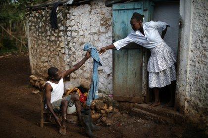 Cristera Jusma le da una toalla a Enol St. Pierre mientras se prepara para ir a la iglesia en Boucan Ferdinand, Haití, el 8 de abril de 2018.
