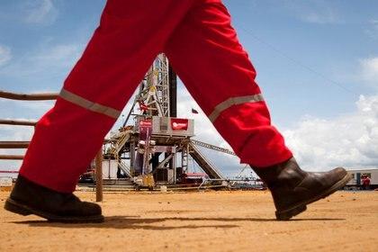 FOTO DE ARCHIVO. Un trabajador pasa junto a una plataforma de perforación en un pozo petrolero operado por la petrolera estatal venezolana PDVSA, en Morichal. 28 de julio de 2011. REUTERS/Carlos Garcia Rawlins.