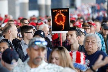 """Un hombre en la multitud sostiene un cartel de QAnon con la abreviatura del grupo de su grito de reunión """"Donde vamos uno, vamos todos"""" mientras la multitud se reúne para asistir al mitin de la campaña del Presidente de los Estados Unidos Donald Trump en el Centro de Convenciones de Las Vegas en Las Vegas, Nevada, EE.UU., el 21 de febrero de 2020 (REUTERS/Patrick Fallon)"""