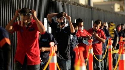 """Imagen de archivo. Empleados de Flex, una empresa que fabrica productos especializados para el sector automotor, ajustan sus mascarillas protectoras a la espera de poder ingresar a la planta durante el primer día de la reapertura gradual de la economía para industrias """"esenciales"""", mientras continúa la propagación del coronavirus en el país. 1 de junio de 2020. REUTERS / José Luis González"""