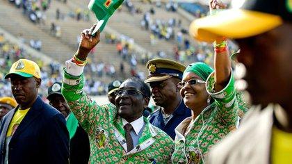 Mugabe y su esposa Grace saludan a sus seguidores en una concentración electoral en Harare en 2013