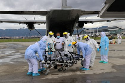 Oficiales de la Fuerza Aérea de Colombia ayudan a un paciente con la enfermedad del coronavirus (COVID-19) a descender de un avión que lo transportó desde la Amazonía colombiana hasta el Comando Aéreo de Transporte Militar CATAM, en medio del brote de la enfermedad del coronavirus (COVID-19) en Bogotá.