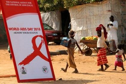 Niños pasan junto a una pancarta durante una campaña de sensibilización sobre el VIH/SIDA con motivo del Día Mundial del SIDA en el campamento de desplazados internos de Kuchingoro en Abuja, Nigeria. África es el continente más golpeado por esta pandemia. (REUTERS/Afolabi Sotunde)