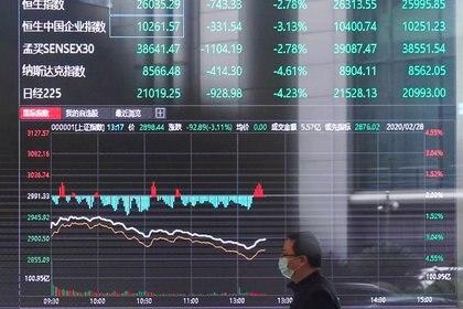 Hombre con mascarillas en el edificio de la Bolsa de Valores de Shanghái, China, 28 febrero 2020. REUTERS/Aly Song