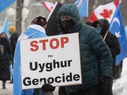 Manifestantes se expresan contra China frente a los edificios del Parlamento en Ottawa, Ontario, por el genocidio de la etnia musulmana uigur. (Adrian Wyld / The Canadian Press vía AP)