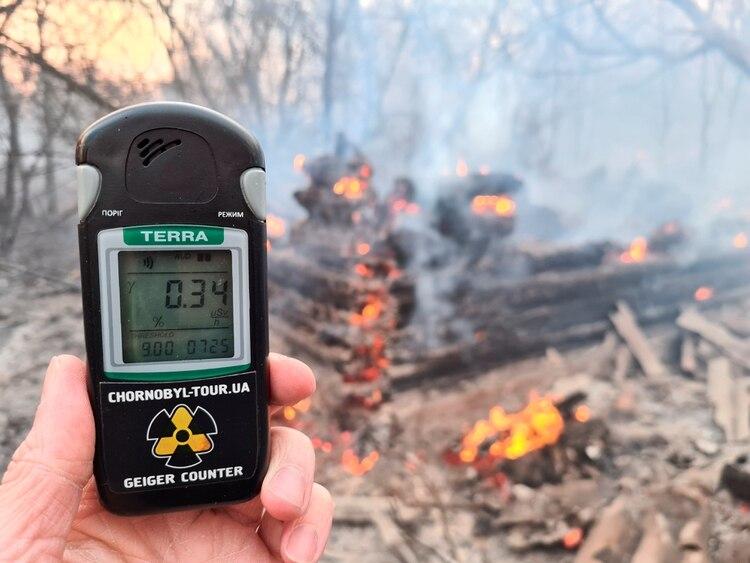 Un contador geiger mide el nivel de radiación en un sitio de incendio en la zona de exclusión alrededor de la central nuclear de Chernobyl, en las afueras de la aldea de Rahivka, Ucrania, 5 de abril de 2020. Fotografía tomada el 5 de abril de 2020. (REUTERS / Yaroslav Yemelianenko)