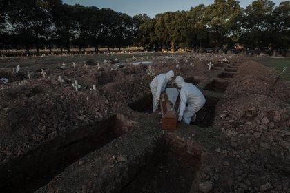 Dos sepultureros cargan un ataúd de una víctima de COVID-19 durante su funeral en el cementerio de Caju este viernes en la zona norte de Río de Janeiro (Brasil). EFE/Antonio Lacerda