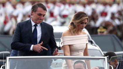 Jair Bolsonaro realiza su gesto característico simbolizando un arma al arribar a la ceremonia de asunción junto a su esposa Michelle (Reuters/Archivo)