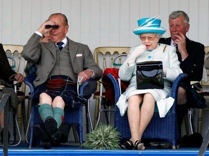 La reina Isabel de Gran Bretaña se aplica lápiz labial. A su lado está su esposo, el príncipe Felipe. La imagen fue tomada durante un evento en Escocia el 3 de septiembre de 2011