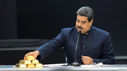 El dictador Nicolás Maduro junto a cinco lingotes de otro, parte de la reservas de Venezuela (Reuters)
