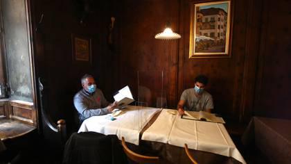Dos personas compartes en una mesa, separados por acrílico, en Bozen, norte de Italia (AP/Matthias Schrader)